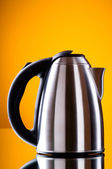 Shiny kettle against the colorful gradient background — Stock Photo