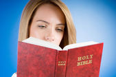 Religion concept - Young girl reading holy bible — Stock Photo