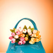 Bag and flowers against the colorful background - Stock Photo