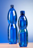 Bottle of water against colorful gradient background — Stock Photo