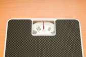 Dieting concept with scales on the wooden floor — Stock Photo