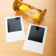 Blank instant photos and hour glass on the wooden table — Stock Photo
