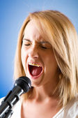 Girl singing with microphone against gradient background — Stock Photo
