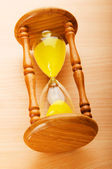Time concept - hourglass against the wooden background — Stock Photo