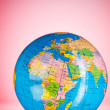 Globalisation concept - globe against gradient colorful backgrou - Stock Photo