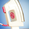 Modern electric iron against the colorful background - Stockfoto