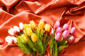 Many flowers on the red satin background — Stock Photo