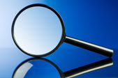 Magnifying glass with wooden handle on the flat surface — Stock Photo