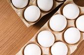 Ahşap masa üzerinde birçok beyaz yumurta — Stok fotoğraf