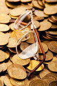 Many coins and reading glasses as business concept — Stock Photo