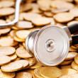 Постер, плакат: Concept of expensive healthcare with coins and stethoscope