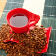 Cup of coffee with many beans around - Foto Stock