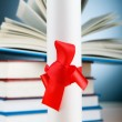 Diploma and stack of books against the background — Foto Stock