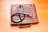 Doctor's case with stethoscope against wooden background — Stock Photo