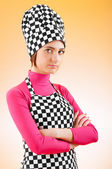 Young female cook against gradient background — Stock Photo