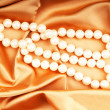 Royalty-Free Stock Photo: Pearl necklace on the bright satin background