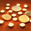 Burning candles and pebbles for aromatherapy session - Стоковая фотография