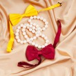 Bow ties and pearl necklace on the satin — Stock Photo