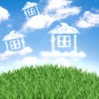 Cloud houses in the air over grass field — Stock Photo