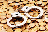 Hand cuffs and coins as security concept — Stock Photo