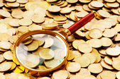 Magnifying glass and coins at the background — Stockfoto