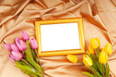 Picture frames and tulips flowers on satin — Stock Photo