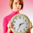 Young woman holding round clock in the hands — Stock Photo