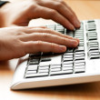 Two hands working on the silver keyboard — Stock Photo #5135064