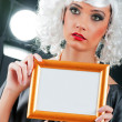 Young attractive girl with blank picture frame — Stok fotoğraf