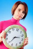 Mujer joven con reloj redondo en las manos — Foto de Stock