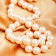 Pearl necklace on the bright satin background — Stock Photo