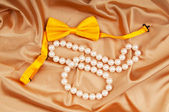 Bow ties and pearl necklace on the satin — Foto de Stock