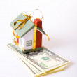 Miniature house over money — Stock Photo
