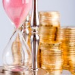 Hourglass and coins — Stockfoto #5259598
