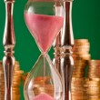 Hourglass and coins — Stockfoto #5259600