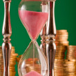 Hourglass and coins — Stock Photo #5259600