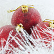 Three red Christmas ball in tinsel - Stock Photo