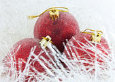 Three red Christmas ball in tinsel — Stock Photo