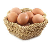 Easter eggs in brown basket on a white background — Stock Photo