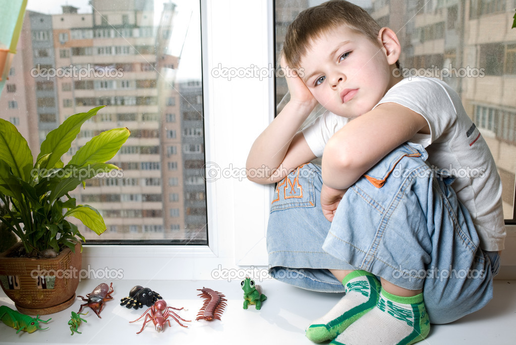 The kid was sitting on the window is very sad, surrounded by toy beetles  Stock Photo #4670767