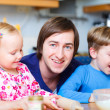 Father with two kids at kitchen — Stock Photo