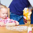 Toddler girl helping at kitchen — Stock Photo