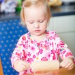 Little girl helping at kitchen - Stock Photo