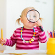 Toddler girl looking through magnifier — Stock Photo