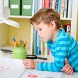 Stock Photo: School boy doing homework at home