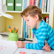School boy doing homework at home - Stock Photo