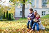 Mother and kids at autumn park — Stock Photo