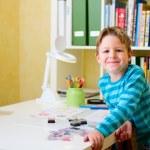 Happy school boy doing homework — Stock Photo