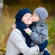 Boy kissing his mother outdoor — Stock Photo