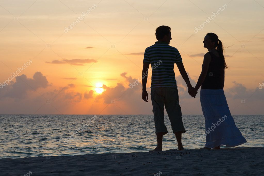 Silhouettes of romantic couple on tropical beach at sunset — Stok fotoğraf #4046011